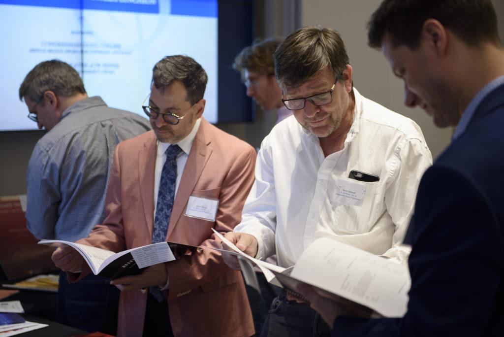 Three men examine printed sheet music